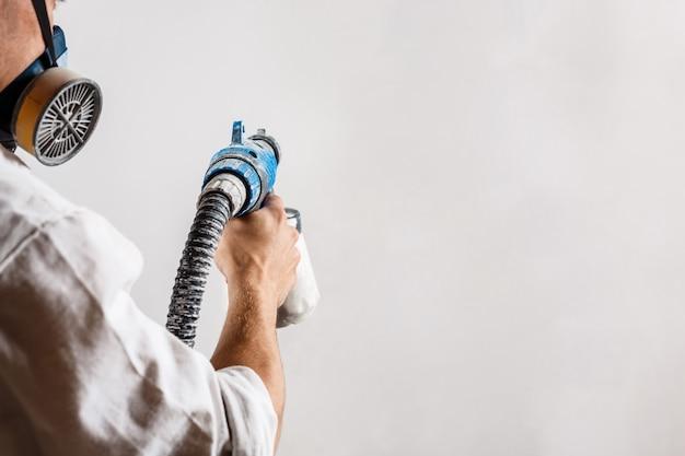 白い色のスプレーガンで労働者の絵画の壁。