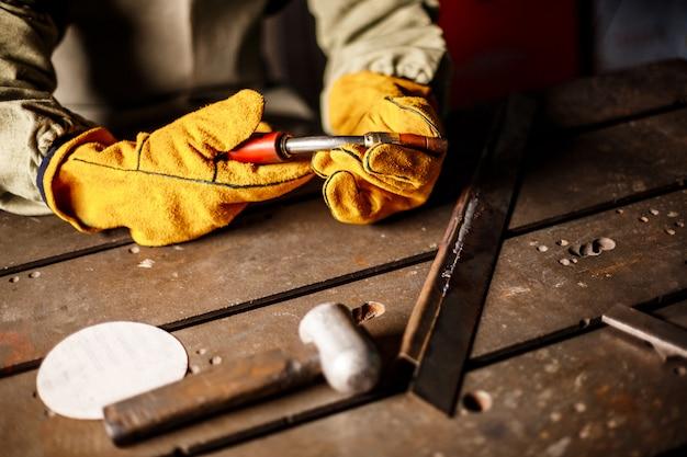 製鉄工場でプラズマ装置を保持している労働者。
