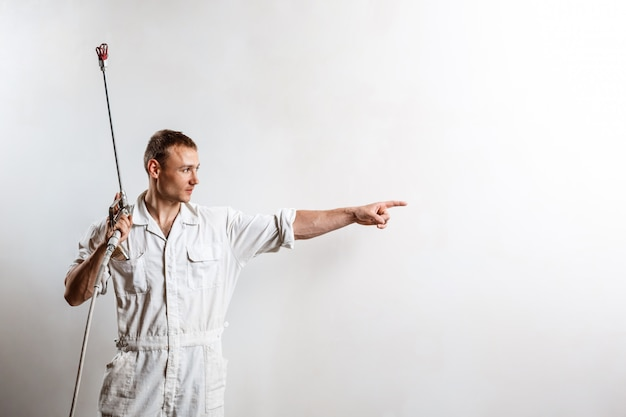 白い壁にスプレーガンを保持している労働者。