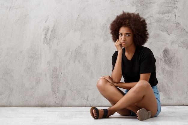 Расстроенная красивая африканская девушка сидя над светлой стеной.
