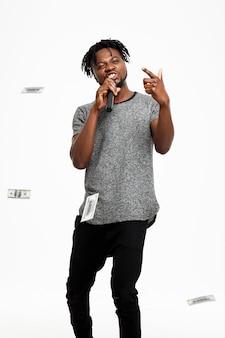 Молодой африканский человек поя в микрофоне на белизне.