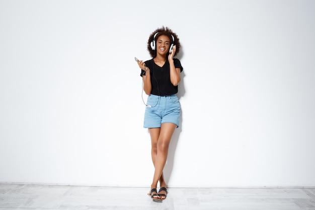 Музыка красивой африканской девушки слушая в наушниках над белой стеной.