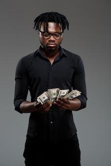 Молодой успешный африканский бизнесмен держа деньги на темноте
