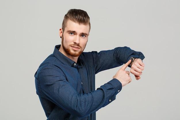 Молодой успешный бизнесмен, указывая на часы над серой стеной.