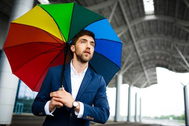 通りでカラフルな傘を保持している青年実業家の写真