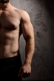 Спортивное мужское тело над темной стеной.