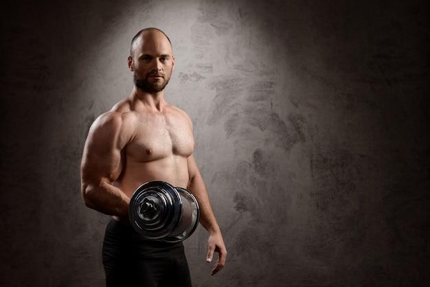 暗い壁の上のダンベルトレーニングの若い強力なスポーツマン。