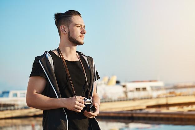 Открытый снимок молодого красивого мужского фотографа, стоящего в гавани, смотрящего, как закат отражается на море и волнах, мечтая или выдумывая идею сфотографировать красивый пейзаж с камерой