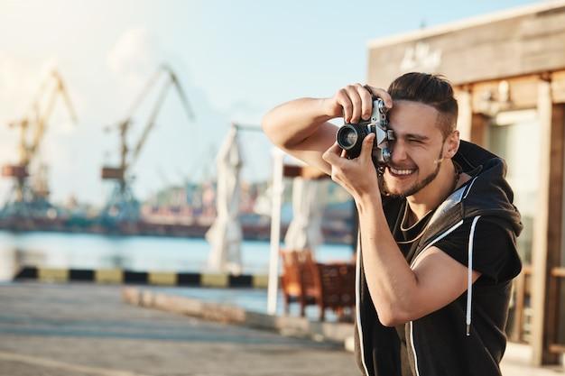 魅力的な若い男性カメラマン、港を歩き、クールなヨットと人々の写真を撮り、素晴らしいショットに焦点を当てたカメラを通して見、フォトジャーナリズムの才能を持っている