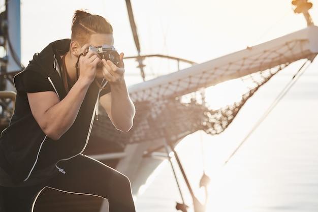 男は最高のショットを探しています。カメラを通して見ているヨット曲げ近くに立って、海や港の写真を撮る、ライフスタイルのコンセプトでショットを撮る作業中に焦点を当てた写真家