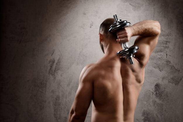 Молодой мощный спортсмен тренировки с гантелями над темной стеной.
