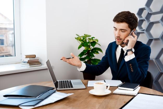 電話、オフィスの背景で話す若い成功した実業家。