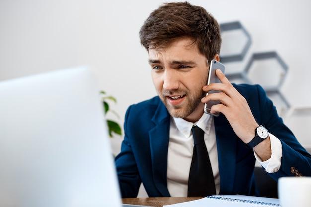 電話、オフィスの背景で話す腹が立つ青年実業家。