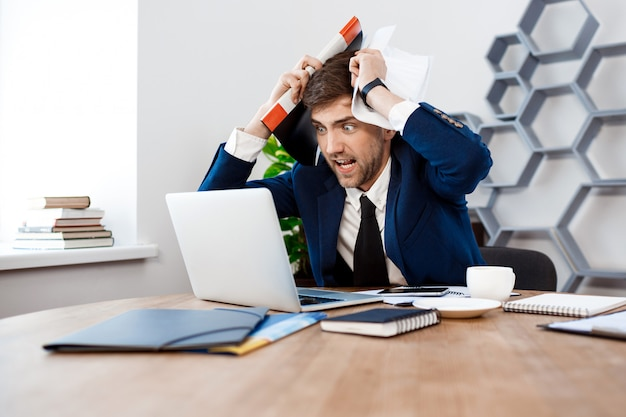 ノートパソコン、オフィスの背景を見て怒っている青年実業家。
