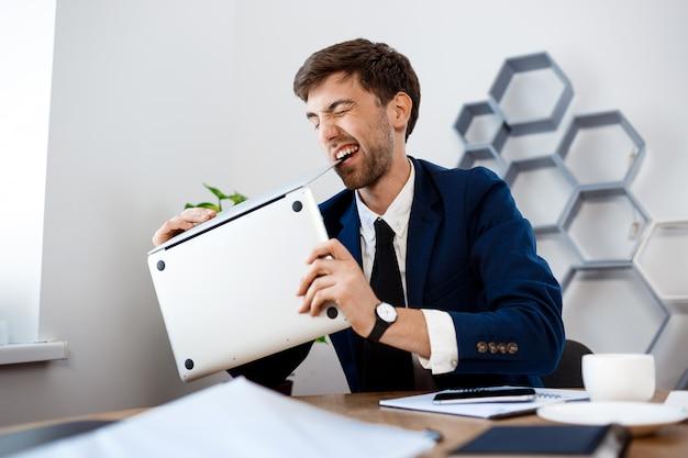 Сердитый молодой бизнесмен грызть ноутбук, офис фон.