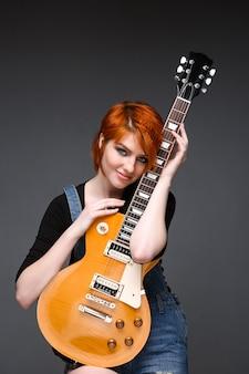 Портрет молодой девушки с гитарой на сером фоне.