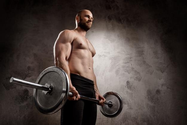暗い壁の上のバーベルでトレーニングする若い強力なスポーツマン。