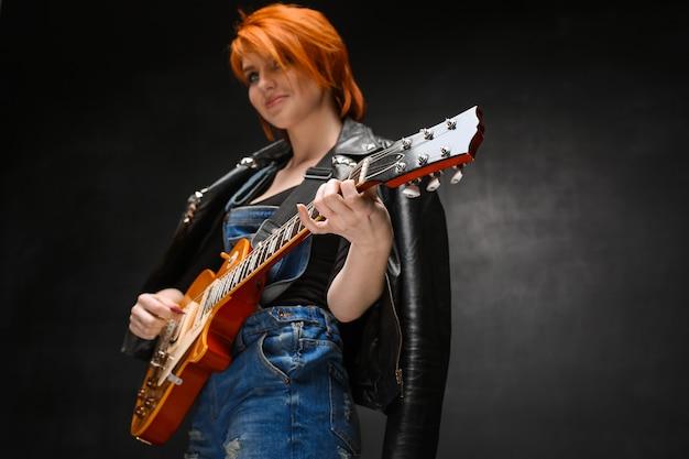 Портрет молодой девушки с гитарой на черном фоне.