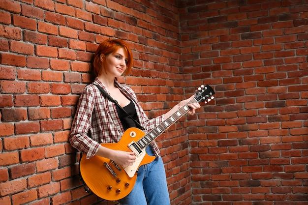 Портрет молодой девушки с гитарой на фоне кирпича.