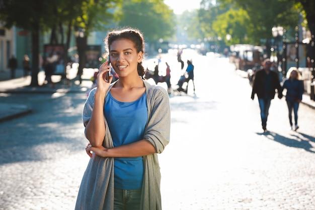 Красивая веселая темнокожая девушка разговаривала по телефону