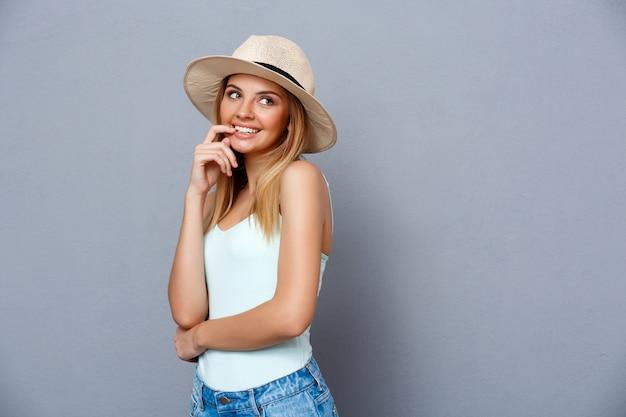 Портрет молодой красивой девушки над серой предпосылкой. копировать пространство