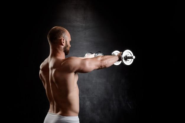 若い強力なスポーツマンが黒い壁にダンベルでトレーニングします。