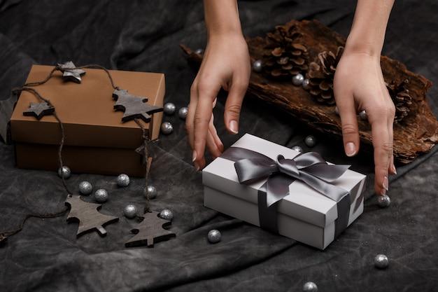女の子の手はテーブルにギフトボックスを置きます。クリスマスの装飾の背景。