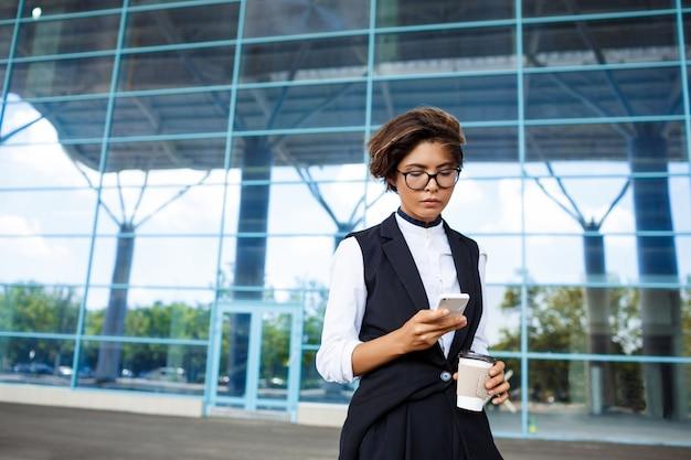 Молодой успешный бизнесмен, глядя на телефон, стоя возле бизнес-центра.