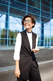 Молодой успешный бизнесмен улыбается, стоя возле бизнес-центра.