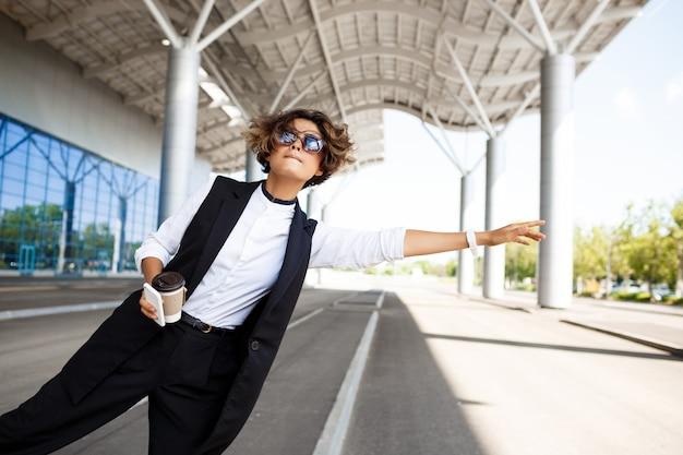 Молодая успешная коммерсантка в солнечных очках заразительных автомобилей над бизнес-центром.