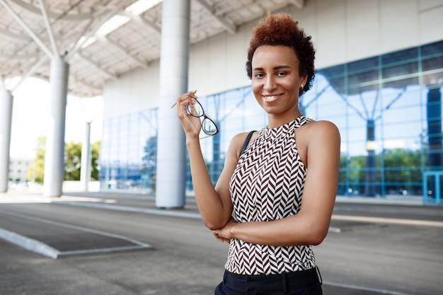 ビジネスセンターの近くに立って、眼鏡を保持している若い成功したアフリカの実業家。