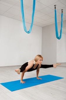 Йога молодой красивой белокурой девушки практикуя в спортзале.