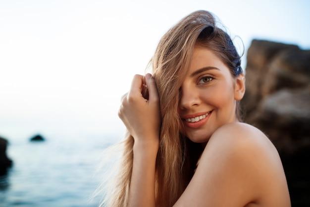 朝のビーチにかかっている美しい陽気な少女