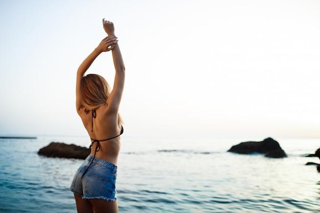 朝のビーチにかかっている美しい若い女の子