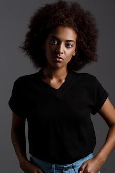 暗い壁の上の美しいアフリカ少女の肖像画