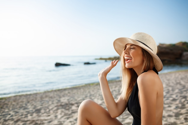 朝のビーチでかかっている帽子の美しい陽気な少女