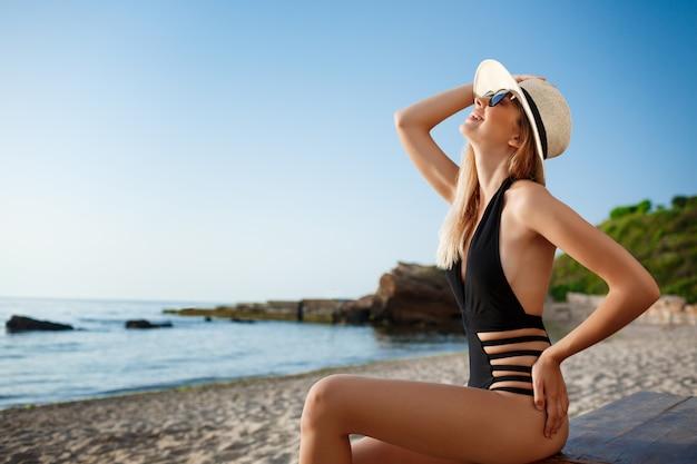 朝のビーチにかかっている帽子とサングラスで美しい陽気な少女