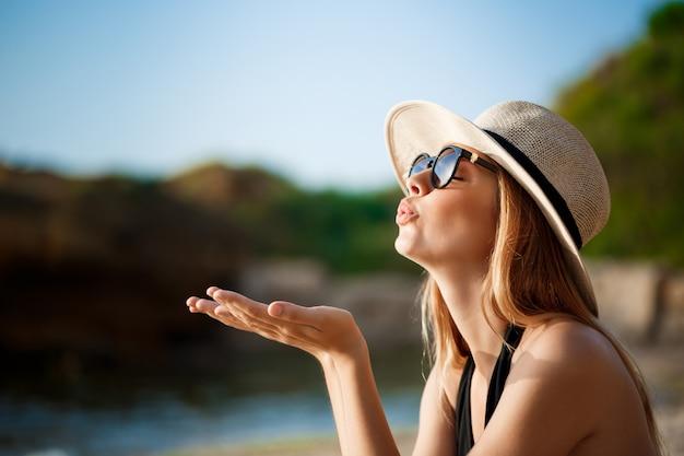 メガネと帽子を身に着けている美しい陽気な少女は朝のビーチにかかっています。
