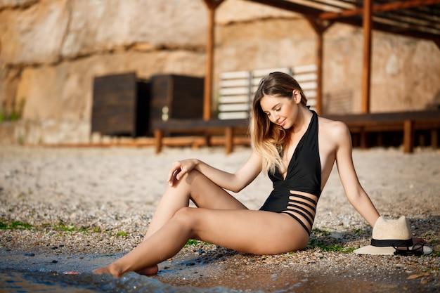 朝のビーチで残りの美しい陽気な少女