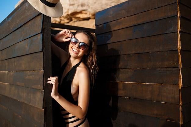 Красивая молодая жизнерадостная девушка в очках лежит на утреннем пляже
