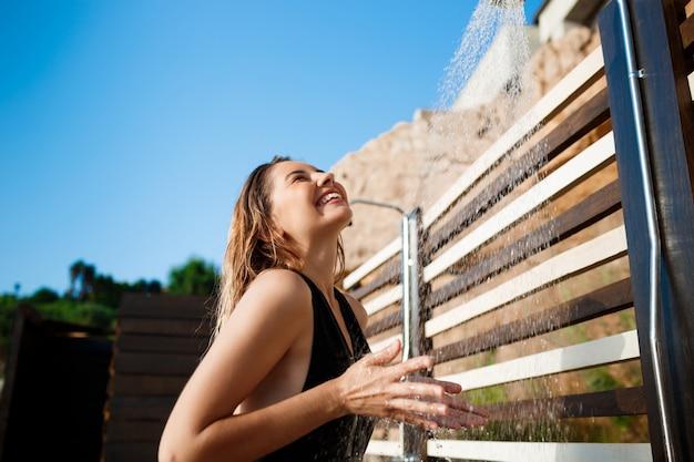 Красивая молодая девушка, одетая в купальники, принимая душ на пляже