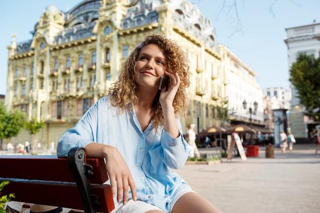 Молодая красивая девушка, выступая на телефоне, сидя на скамейке.