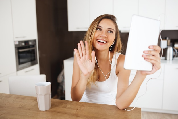 Привлекательная улыбающаяся молодая девушка сидит за обеденным столом, держа планшет и разговаривая с друзьями через мессенджер
