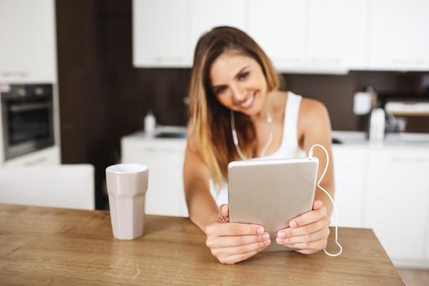 Привлекательная молодая девушка сидит за обеденным столом и делает селфи с планшета