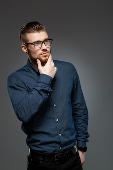 Молодой успешный бизнесмен представляя над темной стеной.