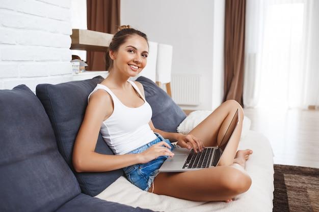 Привлекательная девушка улыбается сидя в гостиной и держа ноутбук.