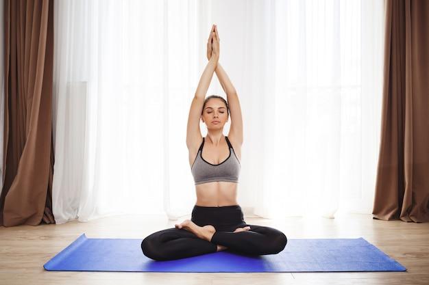 Красивая молодая девушка делает упражнения йоги на полу