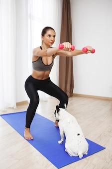 美しいフィットネス女の子はスポーツの練習をし、犬を見て