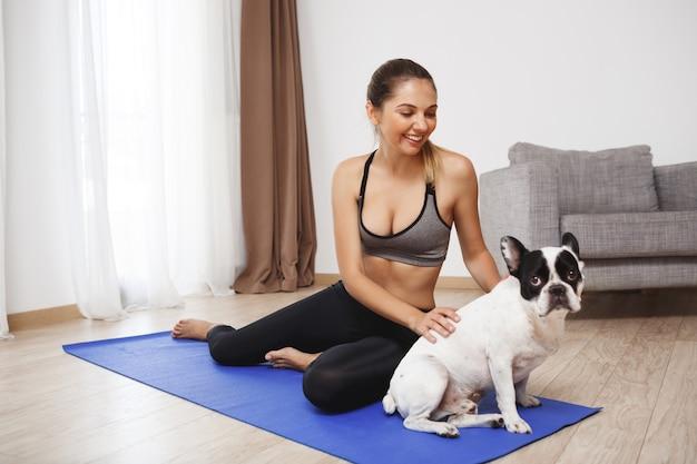 犬と一緒に床に座って美しいフィットネス女の子
