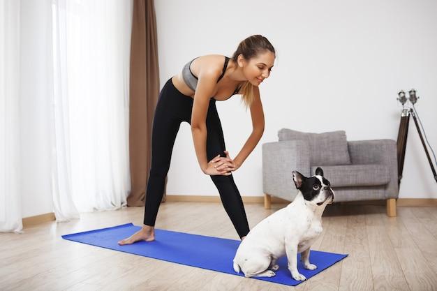 美しいフィットネス女の子は犬と一緒にスポーツ演習を行います